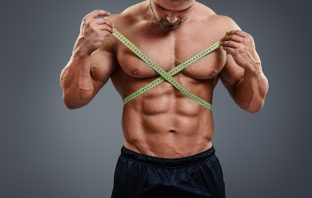 Bodybuilder messt seine Maße, Sixpack